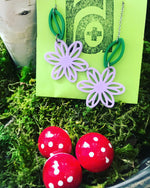 Load image into Gallery viewer, Sitting in a bed of green moss with red and white mushrooms is an R+D necklace on a card. The necklace is 3d printed and has two light purple flowers and two kelly green  leaves.