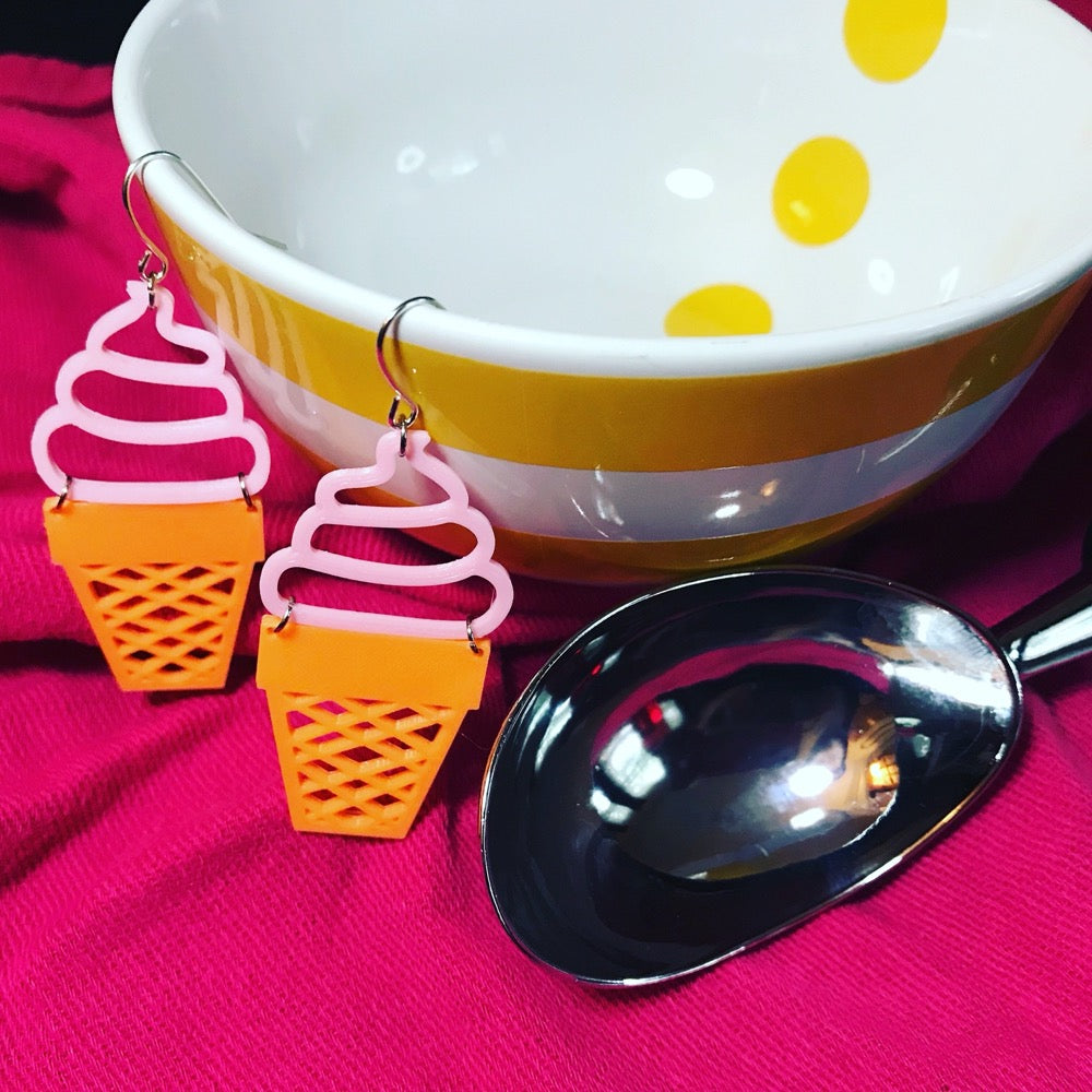 Two quirky earrings are hanging off of an empty bowl and next to a ice cream scoop. The earrings are made of a plant based polymer and have pink swirled soft serve on top of an orange sugar cone.