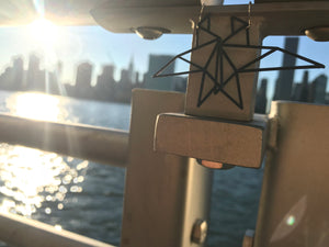 With the sun setting on the manhattan skyline in the background, there are two 3D printed R+D earrings hanging from the railing. They are both black and in the shape of geometric birds.