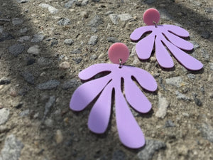 Resting on a sidewalk are two R+D earrings: they have a circlar piece at the top linked to an abstract shape based on Matisse's cut out work. This set is shown in light pink and light purple plant based filament.