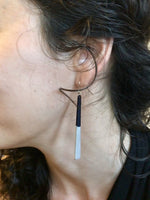 Load image into Gallery viewer, A close up shot of an ear and curly hair. Hanging from her earlobe is a  long minimalist dangle earring. They are a black plant based material that have been dipped into a metallic silver paint to make them shimmery.
