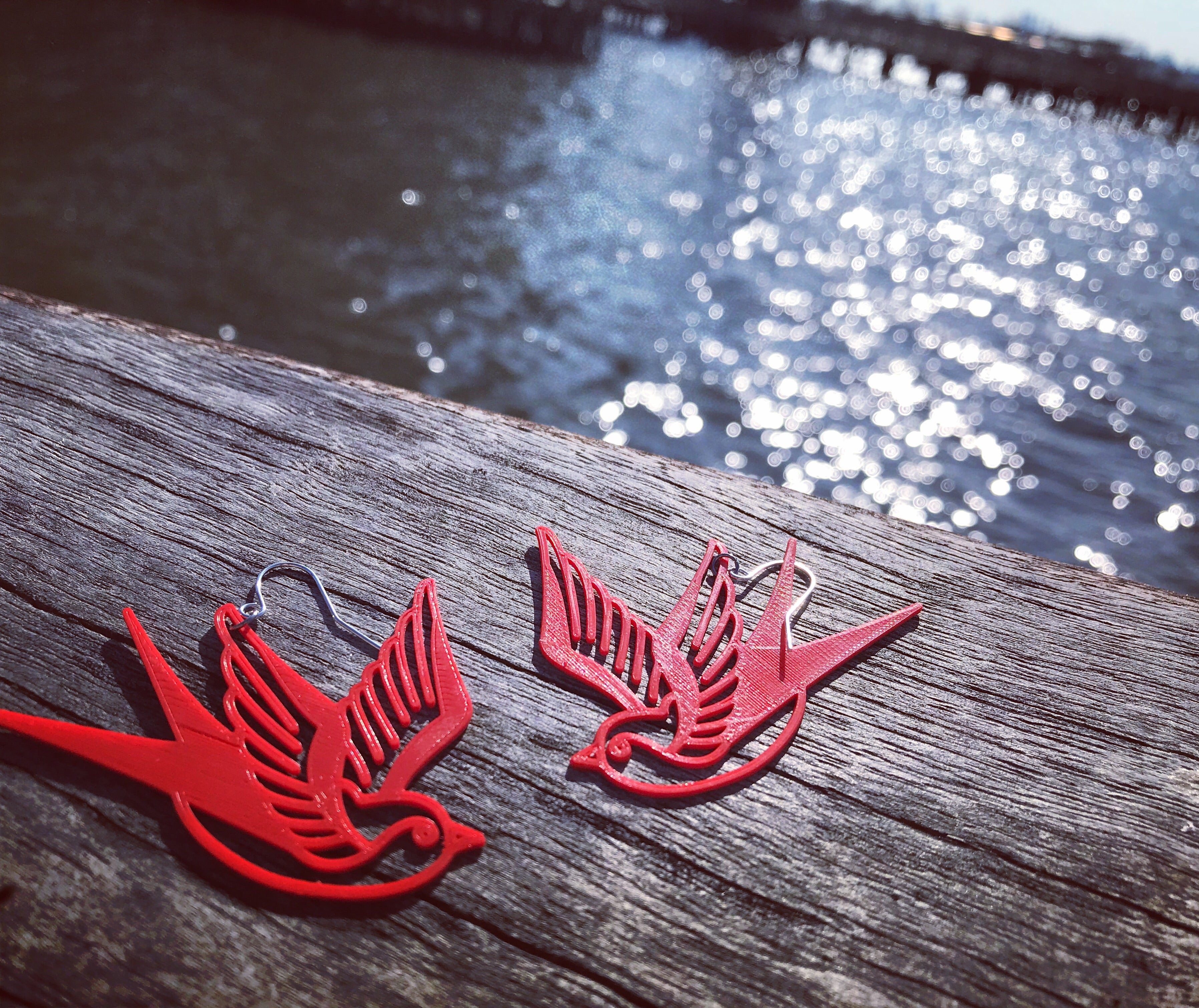 Shown on a wooden pier with the shimmering water in the background are two 3D printed R+D earrings. They are a bright fire engine red color and shaped like  swallows or sparrows. The birds are a classic look like sailor tattoos that mark one's journey.