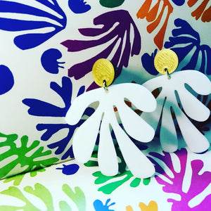 Shown in a box with Matisse's cut out shapes, there are two earrings standing up. The earrings have a circlar piece at the top linked to an abstract shape based on Matisse's cut out work. This set is shown in gold and white plant based filament.