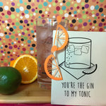 Load image into Gallery viewer, In front of an orange background with multicolor dots .is a cutting board with citrus, a tall glass with ice, gin, and tonic. Hanging off the glass are two R+D earrings. They are orange and shaped like citrus slices with drips of juice. There is also an R+D card that has a glass, ice, napkin and fruit illustrated with the line, You're the Gin to my tonic.