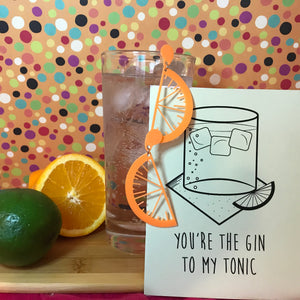 In front of an orange background with multicolor dots .is a cutting board with citrus, a tall glass with ice, gin, and tonic. Hanging off the glass are two R+D earrings. They are orange and shaped like citrus slices with drips of juice. There is also an R+D card that has a glass, ice, napkin and fruit illustrated with the line, You're the Gin to my tonic.