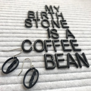 There is a felt letter board that reads, my birthstone is a coffee bean and in the foreground two black plant based earrings that are shaped like coffee beans.