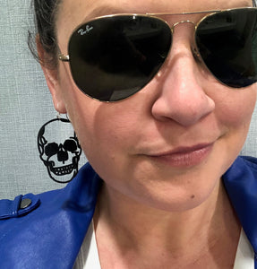 A woman wearing Ray Ban aviator sunglasses and a blue leather jacket smirks at the camera. You can see her skull earring, which forms a perfect black silhouette as it dangles from her earlobe.