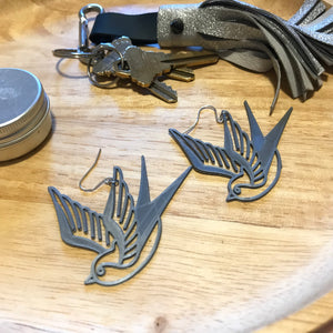 On a wooden catch all dish are a set of keys with a silver leather tassel keychain, an aluminum tin and two silver R+D 3D printed earrings. The earrings are birds that look like they are swooping down. They are reminiscent to classic sailor tattoos of swallows.
