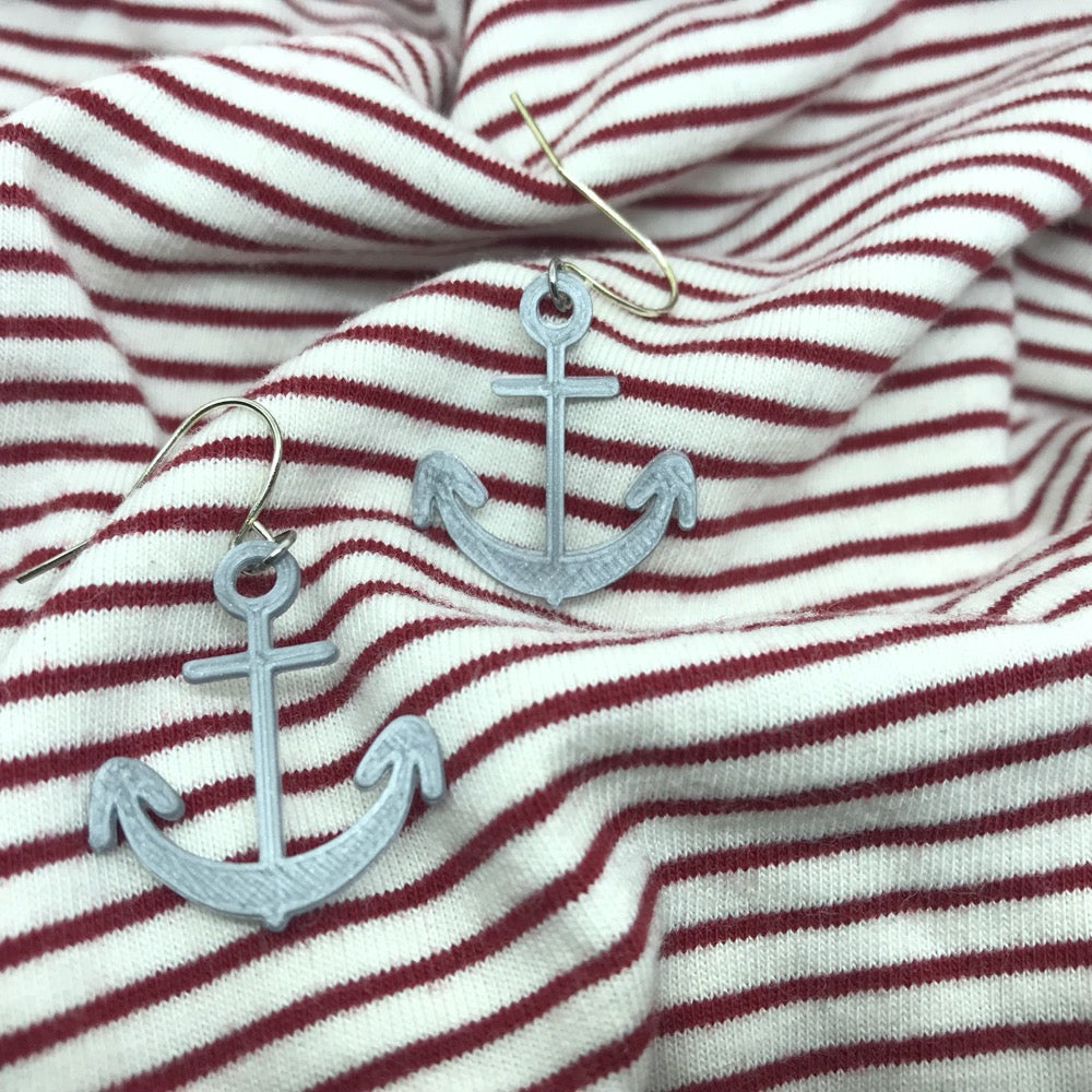 Two silver earrings are shown on red and while striped fabric. The earrings are shaped like boat anchors  and 3D printed.