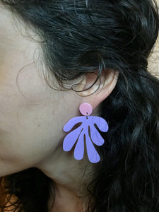 This is a close up of a woman's ear. She is wearing an R+D earring that has a circlar piece at the top linked to an abstract shape based on Matisse's cut out work. This earring is shown in light pink and light purple plant based filament.