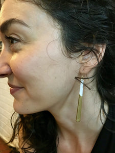 A woman with curly hair smiles as she models long minimalist dangle earrings. They are a white plant based material that have been dipped into a metallic gold paint to make them shimmery.