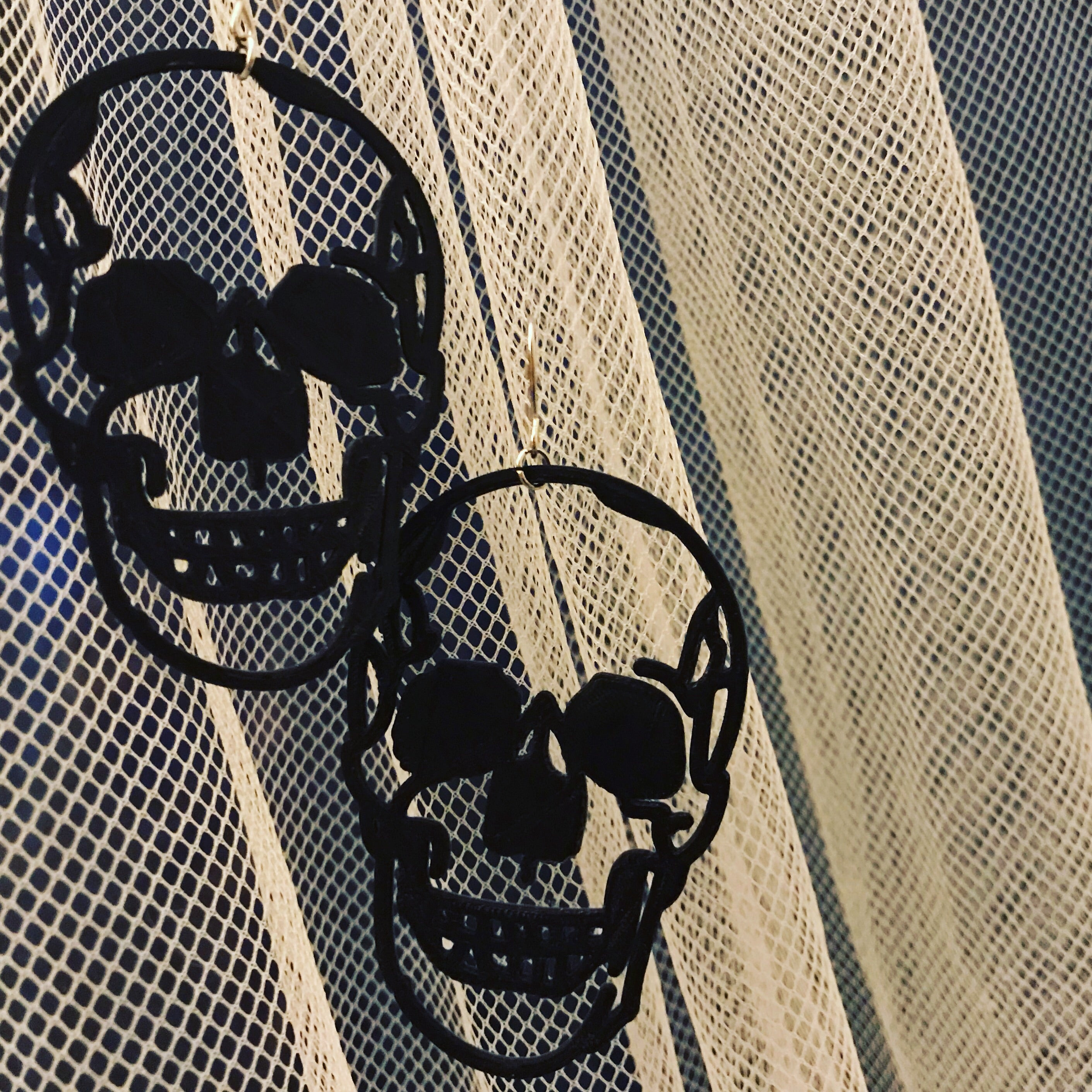 Two earrings are shown on thin, light curtains. The black earrings are shaped like human skulls and are realistic, edgy, and look like they could be smiling.