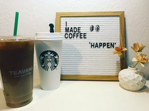 A letter board has the words, I made coffee 'happen'. Also hanging on the letter board are two black earrings shaped as coffee beans. In the foreground are two large Starbuck coffees and a small vase with wooden flowers.
