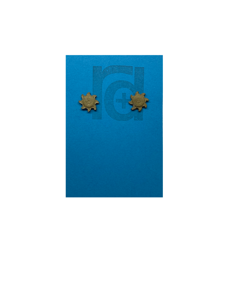 On a bright sky blue earring card with the R+D logo are two 3D Printed studs that are shaped like suns. They are very small and printed in a solid gold color. They have rounded centers and eight beams radiating out from the center. These are printed with an eco friendly material and are biodegradable.