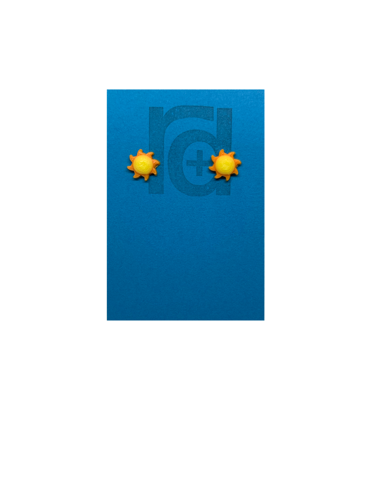 On a bright sky blue earring card with the R+D logo are two 3D Printed studs that are shaped like suns. They are very small, with round yellow centers and eight orange beams radiating out from the center. These are printed with an eco friendly material and are biodegradable.