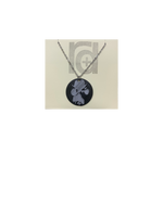 Load image into Gallery viewer, Shown on a tan recyclable necklace card is a 3D printed pendant. The pendant is a black 1 inch circle with a silver paw print. The paw print is from a large dog walking through water and the owner submitting a picture of it.