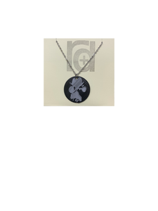 Shown on a tan recyclable necklace card is a 3D printed pendant. The pendant is a black 1 inch circle with a silver paw print. The paw print is from a large dog walking through water and the owner submitting a picture of it.