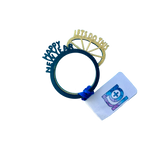 "Load image into Gallery viewer, This is a photo of two stacking R+D rings. They are both 3D printed with delicate details. The one on top is a black ring with the words ""Happy New Year"" sticking up from the band in the same configuration as the classic party crown for New Year's Eve. The ring is gold. It has a crown shape with lines and reads ""Lets Do This"" across the top. When worn and stacked, you can easily read both messages at once."
