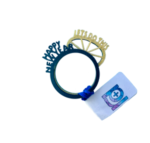 "This is a photo of two stacking R+D rings. They are both 3D printed with delicate details. The one on top is a black ring with the words ""Happy New Year"" sticking up from the band in the same configuration as the classic party crown for New Year's Eve. The ring is gold. It has a crown shape with lines and reads ""Lets Do This"" across the top. When worn and stacked, you can easily read both messages at once."