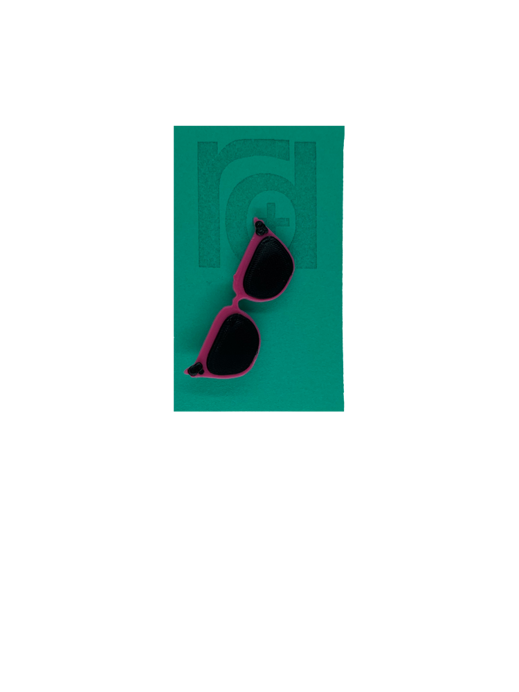 On a teal card is a R+D 3D printed pin. They're in the shape of cat eye sunglasses and have hot pink frames, black lenses, and black accents at the top corners of the glasses.