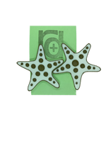Load image into Gallery viewer, Hanging on a green earring card are two large R+D earrings shaped like star fish.  They are white with a gold outline and have circle accents across each arm and in the center.