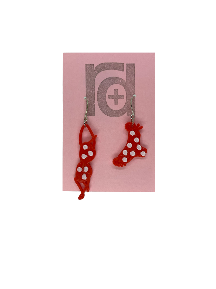 Hanging off of a pink earring card are two R+D earrings. They are asymmetrical  earrings shaped like a classic bikini  that is hung out to dry. The bottoms have ties on the sides. They are red with white polka dots.