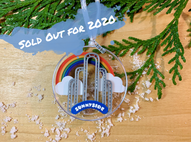 An image of our limited edition ornament for 2020--It features the art deco arch in Sunnyside, Queens, NYC, with a rainbow and clouds behind it. When you flip it over, there is a small fairy door at the borrow of the arch.