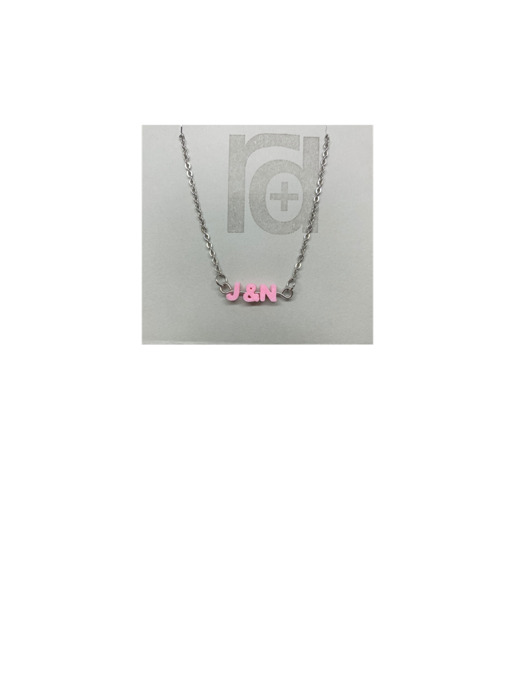 On a grey necklace card is a necklace with small letters on a metal bar. The letters are like beads and will rotate and move around. This necklace has 3 characters (J&N) in a light pink.