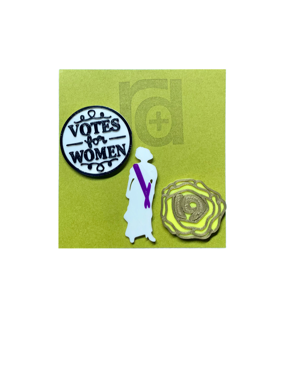 "Shown on a green R+D card are a set of three 3D printed pins. The first on the left is a white circle with a black outline and words saying ""Votes for Women"". The next is a silhouette of a woman from the 1920s. Aside from the silhouette, there is a purple sash. The third pin is a yellow rose, which was worn in support of the movement. The petals are all outlined in gold and in the center is the number 19 for the 19th amendment."