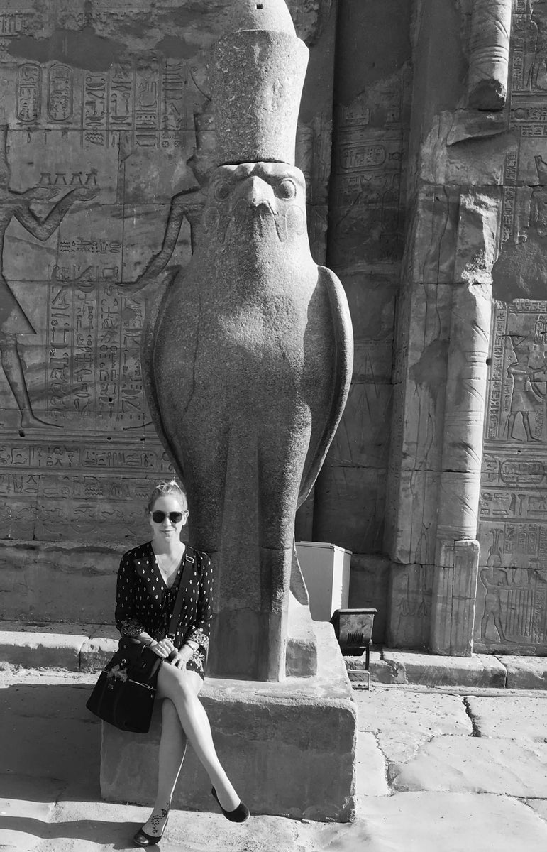 Anuket Founder Ashlee Dozier in Egypt sitting in front of the Temple of Horus in Edfu with a statue of the falcon bird god