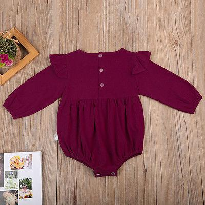 Image of Ruby romper for baby girls, laying flat on wooden backdrop