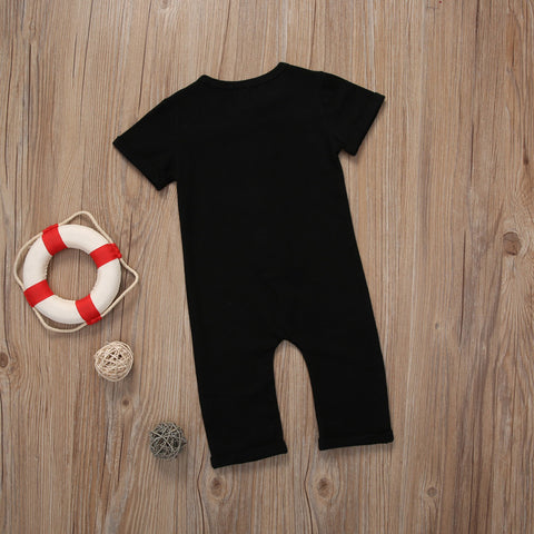 Image of Back of black romper on wooden surface