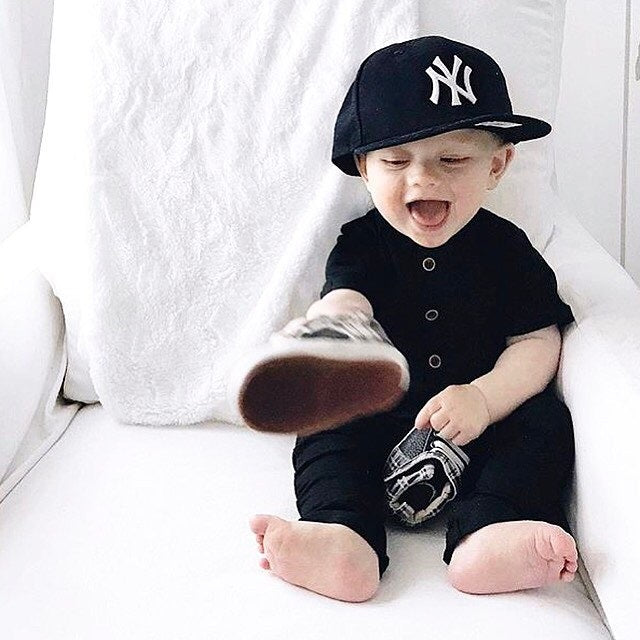 Kid laughing while wearing black romper, NY Yankees baseball hat, and holding out shoes