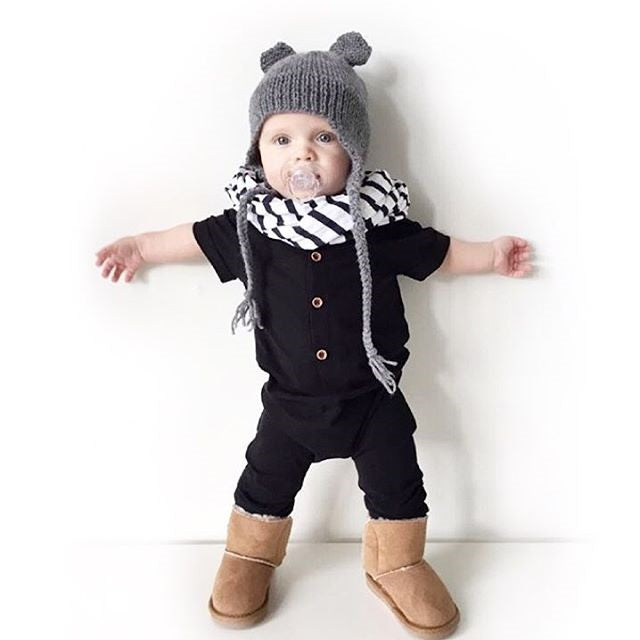 Happy baby with black rompers, striped scarf, and Uggs boots