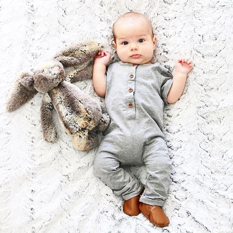 Baby wearing gray romper and holding on to stuff animal