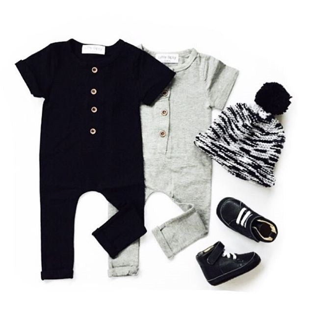 Black and gray rompers with beanie and shoes flatlay