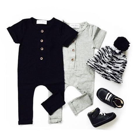 Image of Black and gray rompers with beanie and shoes flatlay