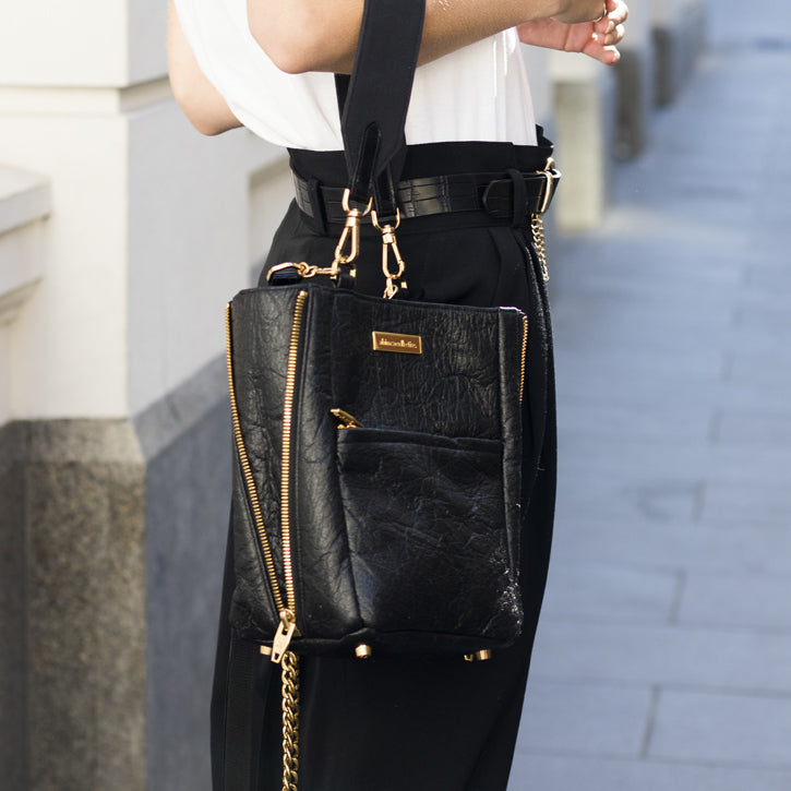 Woman holding black bucket style handbag