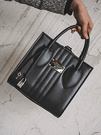 Black handbag being held