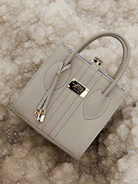 Cream coloured tote style handbag on marble background
