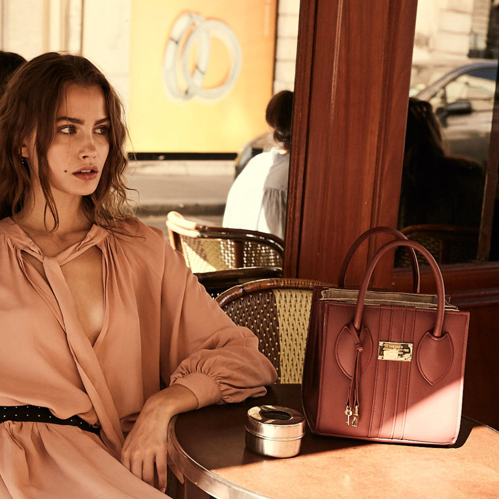 The 1.6 Mini Red tote bag sitting on cafe table with model.