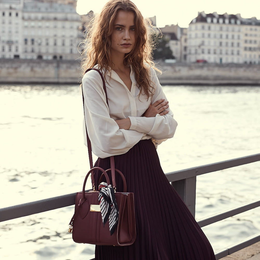The 1.6 Mini Black Apple bag being worn over the shoulder by model on bridge.