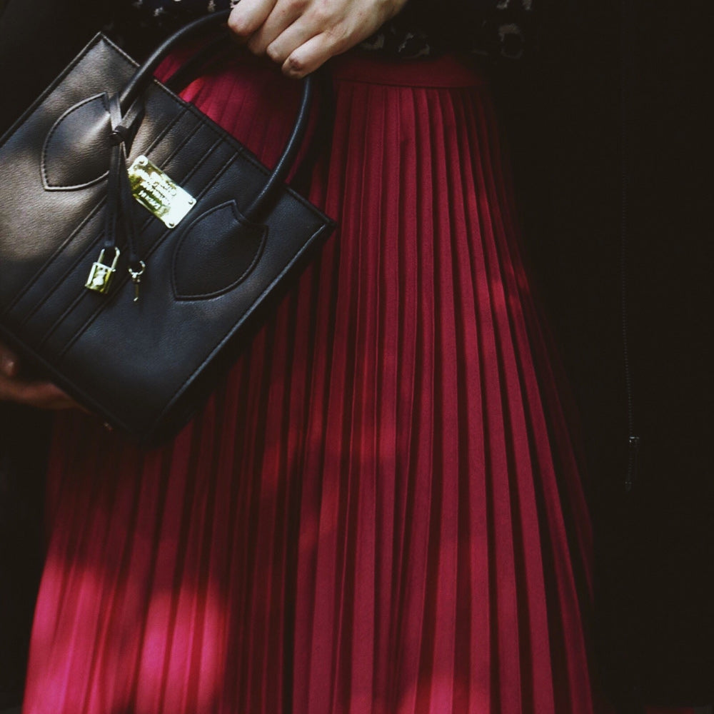 The 1.6 Mini Black Apple bag being held by model in red skirt.