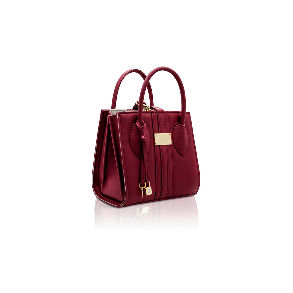 Side angle view of the 1.6 Mini Burgundy bag, a square shaped red vegan tote style bag with gold hardware.