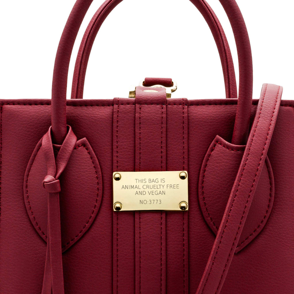 Close up view of gold hardware on the 1.6 Mini Burgundy bag, a square shaped red vegan tote style bag.