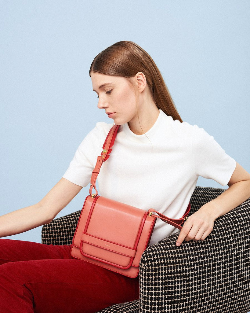 Model sitting with The Fiona Bag Outlines crossbody vegan bag.