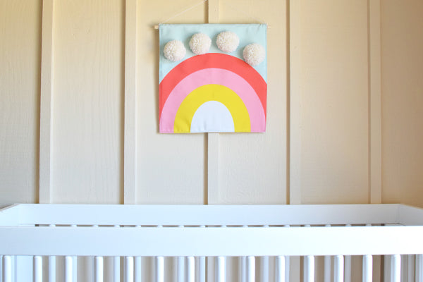 DIY fabric wall hanging with pom poms