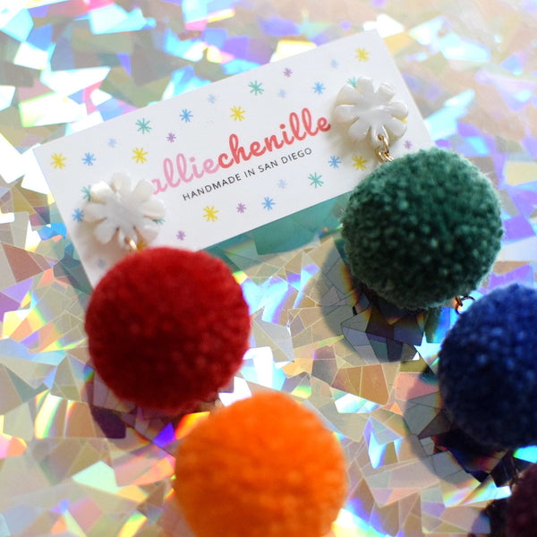 close up of rainbow triple pom pom earrings