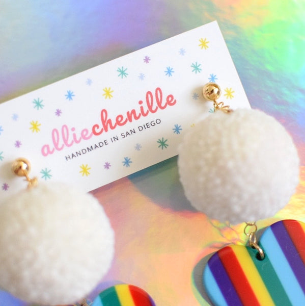 close up of rainbow heart pom pom earrings