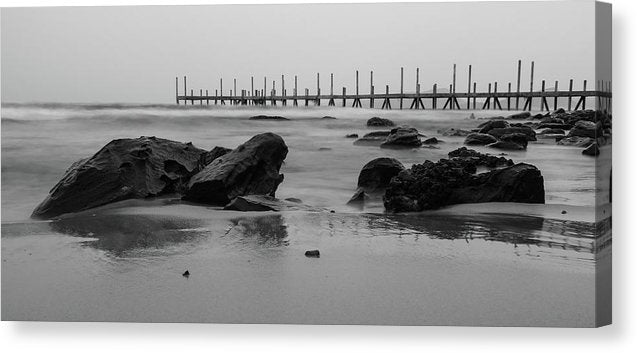 Black Rocks On Sandy Beach With Wooden Pier - Canvas Print from Wallasso - The Wall Art Superstore